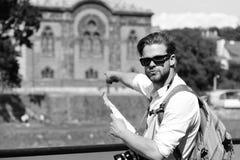Путешествовать и концепция ориентир ориентира Человек с серьезной стороной держит карту и камеру Стоковые Изображения RF