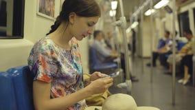 Путешествовать молодой женщины туристский в метро и смотреть в карте на smartphone в метро Бангкока во время каникул Стоковое Изображение