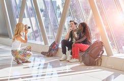 Путешествовать друзья принимая фото одина другого в авиапорте Стоковое фото RF