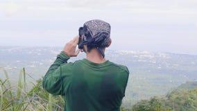 Путешествовать человек принимая панорамное фото к положению мобильного телефона на горном пике Туристское видео стрельбы человека сток-видео