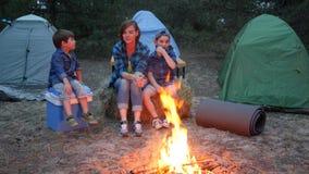 Путешествуйте в лагере, матери и 2 дет сидя вокруг на связке соломы около balefire, мамы и детей связывают близко сток-видео