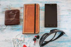 Путешествуйте концепция с бумажником, книгой, сотовым телефоном, стеклами и шлемофоном Стоковая Фотография