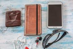 Путешествуйте концепция с бумажником, книгой, сотовым телефоном, стеклами и шлемофоном Стоковое Изображение