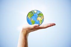 Путешествуйте концепция с рукой человека и круглой землей Стоковые Изображения RF