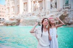 Путешествуйте монетка мамы и девушки семьи trowing на фонтане Trevi, Риме, Италии для удачи Счастливая семья наслаждается их итал Стоковые Изображения RF