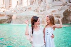 Путешествуйте монетка мамы и девушки семьи trowing на фонтане Trevi, Риме, Италии для удачи Счастливая семья наслаждается их итал Стоковые Изображения