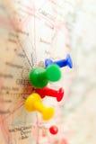 Путешествуйте пункты назначения на карте показанной с красочными канцелярскими кнопками и малой глубиной поля Стоковые Фото