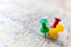 Путешествуйте пункты назначения на карте показанной с красочными канцелярскими кнопками и малой глубиной поля стоковая фотография