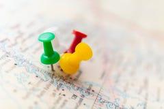 Путешествуйте пункты назначения на карте показанной с красочными канцелярскими кнопками и малой глубиной поля стоковые фотографии rf