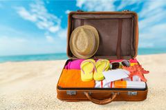Путешествуйте чемодан с шляпой пляжа, кувырками дальше Стоковое фото RF