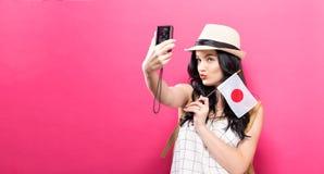 Путешествующ молодая женщина держа камеру с японцем сигнализируйте стоковое фото