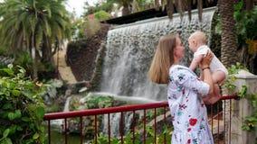 Путешествующ с ребенком, молодая мать играет и обнимает ее сына около водопада Младенец поцелуев на щеке сток-видео