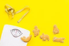 Пути для теряют вес Спорт Печенья в форме asans йоги близко лента вычисляют по маcштабу и измерять на яркой желтой предпосылке Стоковые Фотографии RF