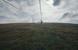 Путь кабеля среди полей на холме стоковое фото