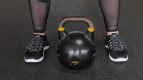 Пухлая женщина в спортзале поднимает черное kettlebell Разработка сток-видео