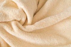 Пушистая бежевая предпосылка полотенца, конец-вверх Ткань нежного младенца пастельная с волнами и створками Сложенная нежная свет стоковое изображение