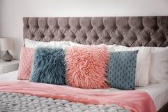 Пушистые подушки на кровати в комнате Стоковые Изображения