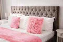 Пушистые подушки на кровати в комнате Стоковые Фотографии RF
