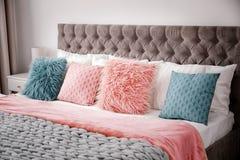 Пушистые подушки на кровати Стоковое Изображение