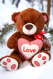 Пушистый милый мягкий плюшевый медвежонок игрушки с влюбленностью сердца в снеге Стоковые Изображения RF