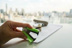 Пулер штапеля зеленого цвета пользы женщины извлекает штапель от документа стоковые изображения