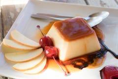 Пудинг и ложка и яблоко на блюде Стоковые Фото