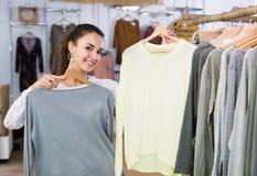 Пуловер excited молодой женщины покупая стоковая фотография