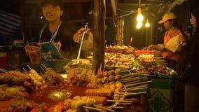 ПХУКЕТ, ТАИЛАНД 9-ое сентября 2018: Азиатский рынок ночи еды Девушка продает мясные продукты сток-видео