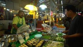 ПХУКЕТ, ТАИЛАНД 9-ое сентября 2018: Азиатский рынок ночи Покупатель покупает овощи от продавца видеоматериал