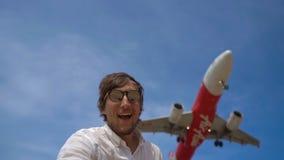 10 02 2019 - Пхукет, Таиланд: Счастливый турист имеет потеху на тропическом пляже с самолетом Air Asia летая над ним акции видеоматериалы