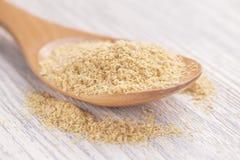 Пшеница проросла семена в деревянной ложке на белом деревянном столе Мякиши разбросали вокруг стоковые изображения rf