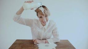 Пылкая привлекательная молодая женщина при вьющиеся волосы держа бутылку золота льет белый югурт на ее стороне с открытым ртом видеоматериал