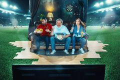 Пылкие вентиляторы сидят на софе и смотрят ТВ в середине футбольного поля стоковые изображения