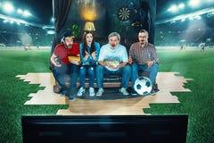 Пылкие вентиляторы сидят на софе и смотрят ТВ в середине футбольного поля стоковые фото