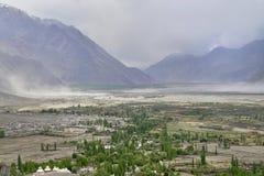 Пыльная буря в широкой широкой долине горы: на переднем плане пышные шири с рекой, зелеными деревьями и белым b Стоковое Фото