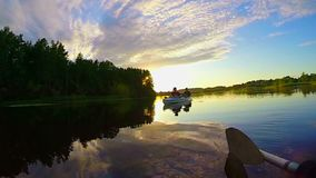 Пышный заход солнца на мирном реке, туристах в шлюпке, природе