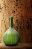 Пылевоздушная бутылка вина установленная против предпосылки grunge Стоковые Фотографии RF