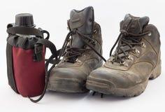 Пылевоздушные пешие ботинки и красная бутылка с водой на белизне Стоковые Фотографии RF