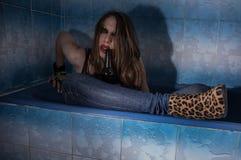 Пьяная девушка лежа в ванне с бутылкой в ее руке стоковые фото