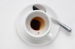 Пьяная чашка кофе с землями кофе на поддоннике против белой предпосылки, взгляд сверху с местом для текста Стоковое Изображение