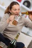 Пьяные детеныши на софе с пивом бутылки в руке Стоковая Фотография RF