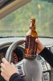 Пьяный водитель женщины с бутылкой выпивки стоковые фото