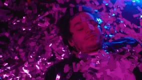 Пьяный человек спать на поле в ночном клубе покрытом с confetti, похмельем партии видеоматериал