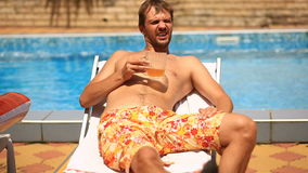 Пьяный человек в шортах выпивая пиво бассейном сток-видео