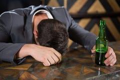 Пьяный человек лежа на счетчике с бутылкой пива стоковое фото