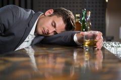 Пьяный человек лежа на счетчике с стеклом вискиа стоковая фотография rf