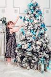 Пятилетняя девушка висит игрушки на рождественской елке стоковые фотографии rf
