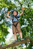 Пятилетний мальчик на веревочк-пути в лесе Стоковые Изображения RF