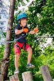 Пятилетний мальчик на веревочк-пути в лесе Стоковое фото RF