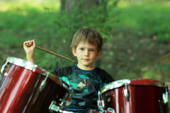Пятилетний старый мальчик уча барабанить outdoors в парке Стоковое Изображение RF
